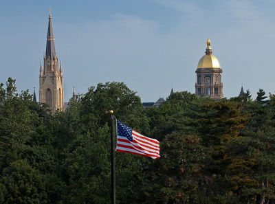 The American flag flies on South Quad in view of the Dome and Basilica.